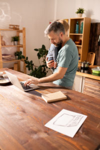 Busy Father Checking Email While Holding Son - Trouvez des solutions avec AMC Ressources, méthode et outils concrets